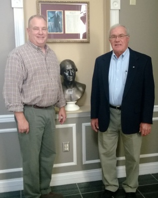 Rev. Geoff Baggett (l) and Chapter President Ken Oakley (r) pose in front of the George Washington bust in the hallway of the Hutton School of Business at the University of the Cumberlands in Williamsburg, Kentucky.