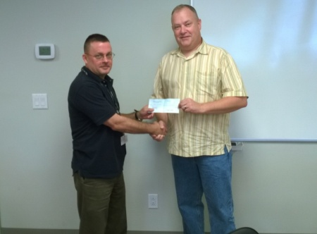 Pennyroyal Veteran's Center Director Jeff Broadbent receives a $1000 check from Crossroads Fellowship Pastor and Col. Stephen Trigg Chapter President Geoff Baggett
