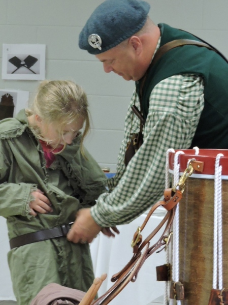 "Geoff Baggett helps a young lady ""suit up"" in a green hunting frock and leather belt."